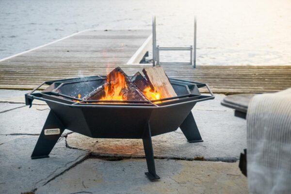 Octagonal shaped backyard fireplace burning wood