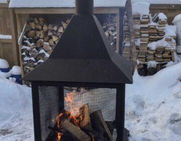 Chiminea in backyard in winter, firewood pile in background