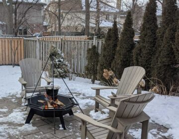 Cottager fire pit in backyard in winter, 3 chairs surrounding it