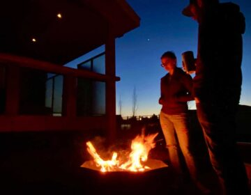 Cupola Fire Pit, lit, in backyard at night with people standing around it