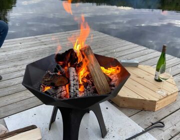 burning Polygon Bowl fire pit on a dock, lake in background