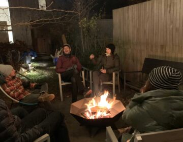 Group of people sitting around a burning Polygon Bowl fire pit