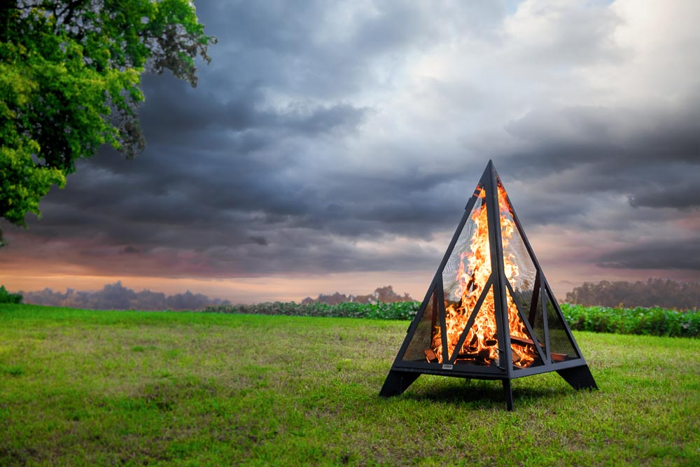 Pyramid outdoor fireplace in field, cloud filled sky