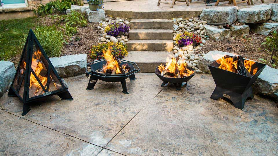 A group of Iron Embers fire pits, with fires lit, sitting on a patio